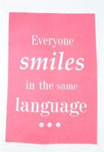 "Astiapyyhe tekstillä ""Everyone smiles in the same language"""